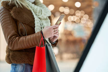 Midsection of adult woman shopping in mall using smartphone wearing a mask Stockfoto