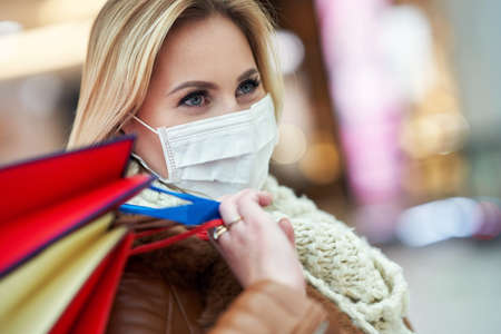 Portrait of adult woman shopping in mall wearing a mask, coronavirus concept Stockfoto