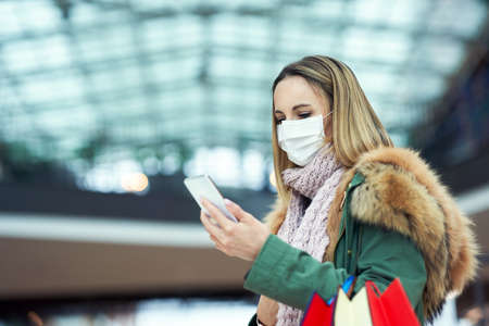 Portrait of adult woman shopping in mall using smartphone wearing a mask Stockfoto