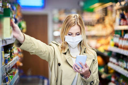 Adult woman in medical mask using smartphone and shopping for groceries