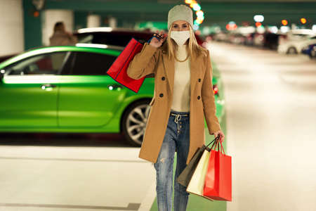 Adult woman with shopping bags in mask in underground parking lot Stockfoto