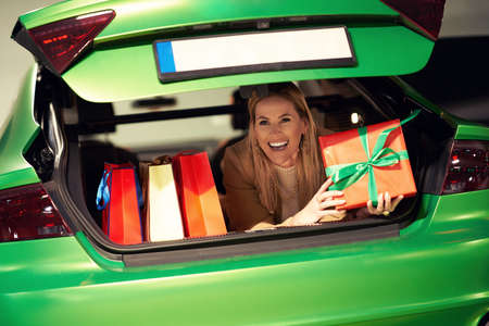 Adult woman with shopping bags lying in trunk