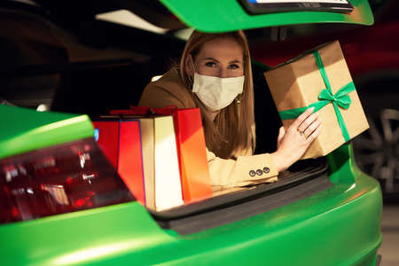 Adult woman with shopping bags in mask lying in trunk
