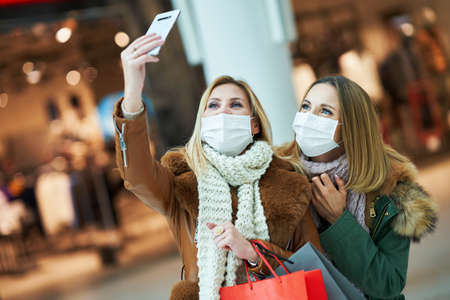 Portrait of two friends shopping together using smartphone and wearing a mask Stockfoto