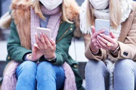 Two women using smartphones and wearing masks in the city Stockfoto
