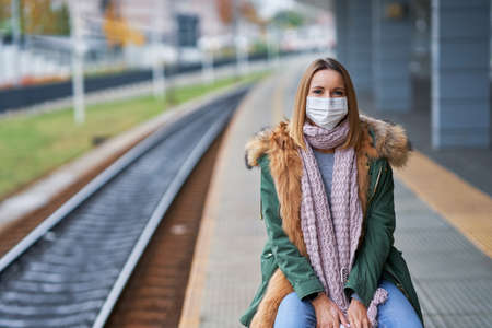 Adult woman at train station wearing masks due to covid-19 restrictions