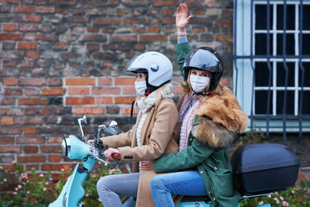 Two women wearing masks and commuting on scooter