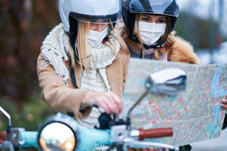 Two women wearing masks and commuting on scooter holding map