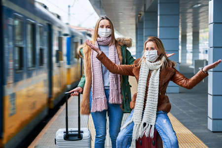 Two women at train station wearing masks due to covid-19 restrictions Stockfoto