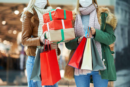 Midsection of two friends shopping together wearing a mask, coronavirus concept Stockfoto