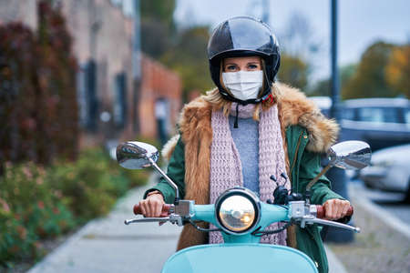 Adult woman wearing masks and commuting on scooter