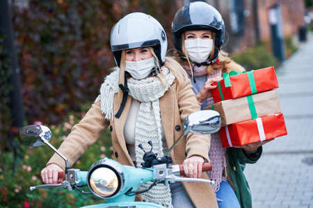 Two women wearing masks and holding shopping bags on scooter