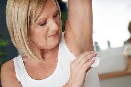 Senior woman using deo roll-on in the bathroom Standard-Bild