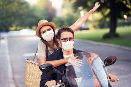 Happy mature couple wearing masks while riding a scooter in the city on a sunny day Archivio Fotografico