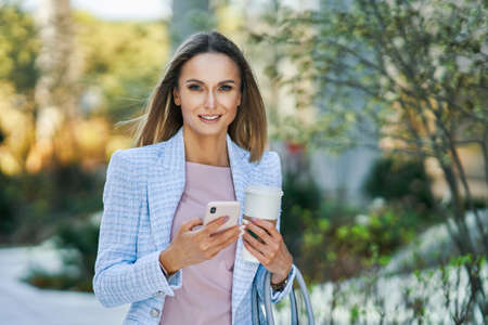 Adult attractive Business woman with smartphone and coffee walking in the city