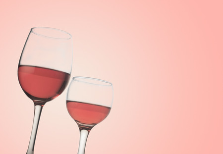 wine  pink: Horizontal front view of two rose wine glasses isolated on pink background Stock Photo