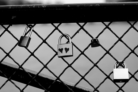 black and white lock: Black and white picture of a metal lock with two hearts written on the front Stock Photo