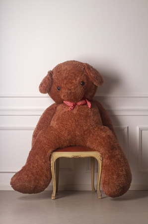 burned out: Huge toy bear with a dotted bow standing on a chair against a white wall