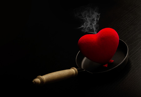 ardor: A red heart smoking on a metal frying pan Stock Photo