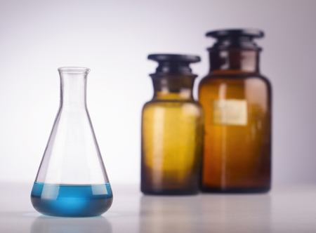alumnos en clase: A medical glass with blue liquid in front of old brown jars