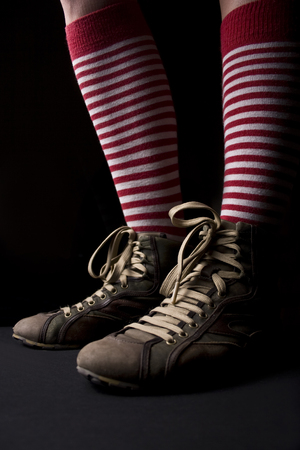 black white red: Woman�s legs with sneakers and a pair of red socks with white stripes on dark background Stock Photo