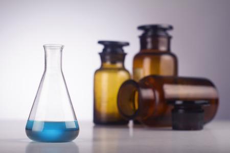 alumnos en clase: Un vaso m�dica con el l�quido azul frente a viejos frascos marrones Foto de archivo