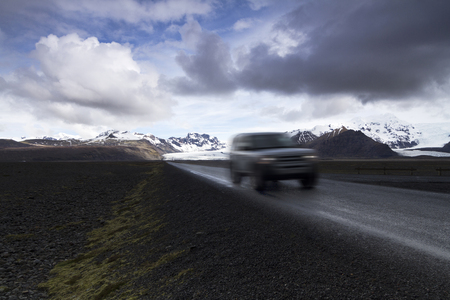 desolated: Horizontal photo of an off road car on a straight asphalt road coming from the mountains with clouds above and the Vatnajokull glacier in the background, Iceland