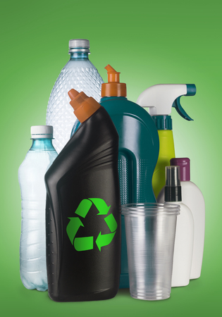 reprocess: Set of different plastic containers on green background with the recycle sign on the front one