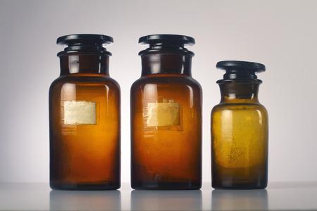 alumnos en clase: Tres viejos médicos frascos de vidrio marrón aislados sobre fondo gris Foto de archivo