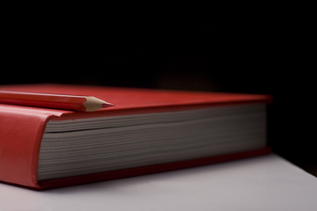 thesaurus: Horizontal side view of a red closed book with a red pencil on top of it