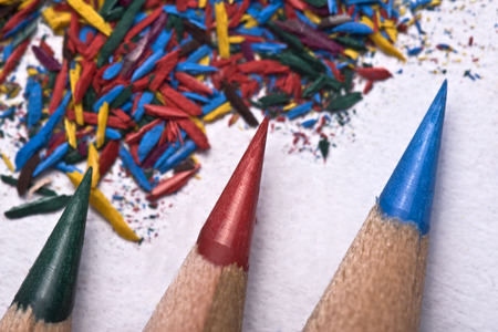 sharpened: Green, red and blue pencil being sharpened on a white piece of textured paper