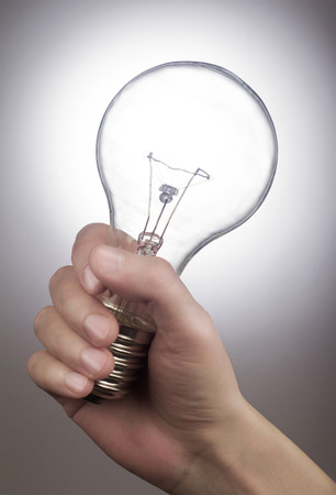 lack of confidence: Hand holding a light bulb on grey background