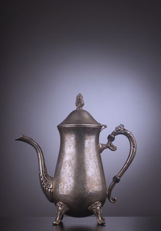 engravings: Silver vintage tea kettle with engravings on gray background Stock Photo