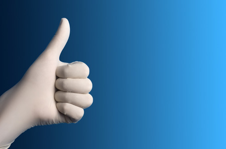 surgical glove: Hand with a white surgical glove showing the ok sign against a blue background Stock Photo