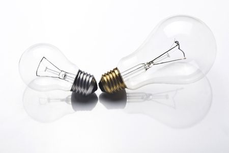 metal filament: A small light bulb with silver screw and a large one with golden screw on white background