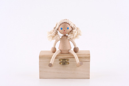 mistery: hand made wooden girl sitting on a wooden chest