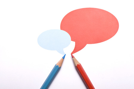 opinionated: Horizontal top view of a red and a blue pencil with speech bubbles of different sizes above them isolated on white background.