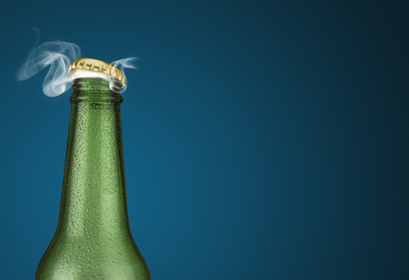 dew cap: Horizontal photo of a green cold beer bottle with water drops and golden cap open on blue background