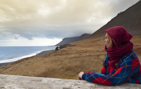 mujer mirando el horizonte: Foto horizontal de una mujer rubia que llevaba una bufanda y un su�ter y mirando a una hermosa costa en Islandia