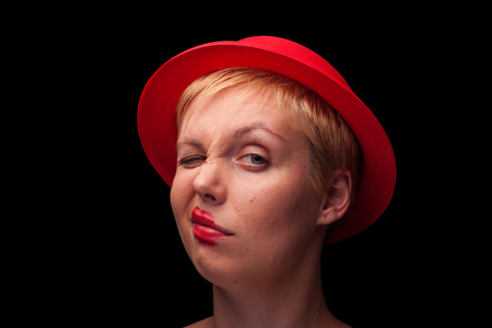 lip stick: horizontal front view portrait of a young blonde woman with red hat making a face on black background Stock Photo