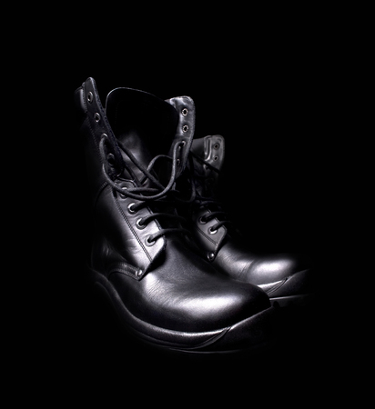 untied: side view of a pair of shiny black leather boots with untied shoe laces on black background Stock Photo
