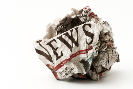 failed politics: Horizontal front view of a ball of twisted newspaper page with the word news visible isolated on white background Stock Photo