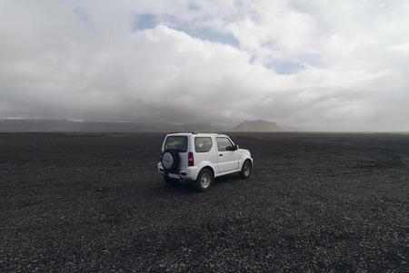off road vehicle: Vik, Iceland - May 22, 2015: White off road vehicle parked on the black beaches near the city of Vik. Driving off road in Iceland with the car is strictly prohibited as the locals try to provide protection for the extremely fragile sub arctic wildlife.