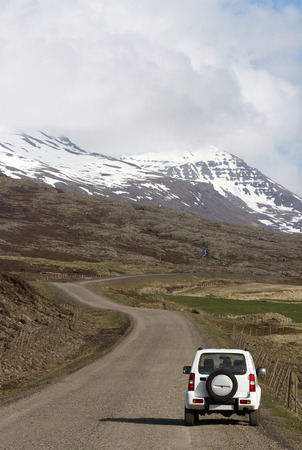 off road vehicle: Snaefellsnes Peninsula, Iceland - May 28, 2015: White off road vehicle parked on the side of a gravel road in Snaefellsnes peninsula.