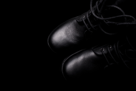army boots: A pair of black army boots with shoe laces on black background Stock Photo