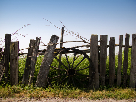 chariot: horizontal front view of an old chariot wheel covering the hole in a wooden fence with a green field behind