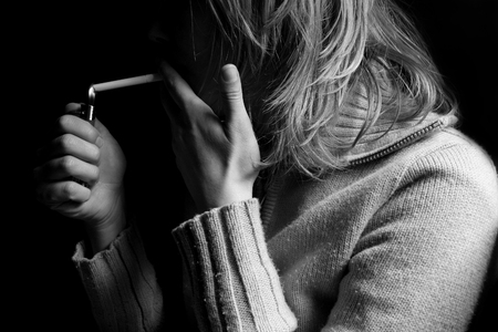 side lighting: horizontal side view of a young blonde woman lighting a cigarette and smoking in the dark Stock Photo