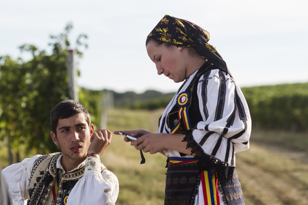 fair woman: Jidvei, Romania - September 22, 2012: A young man and a woman with traditional Romanian garments at the annual vineyard harvest fair. Woman is checking her mobile phone while the man is watching her. Editorial