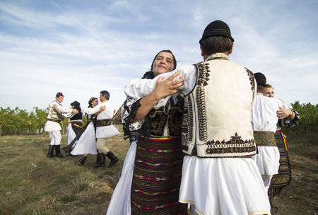 Jidvei, Romania - September 22, 2012: People in traditional Romanian costumes dancing at the annual vineyard harvest fair. Jidvei is one of the biggest Romanian wine producers.