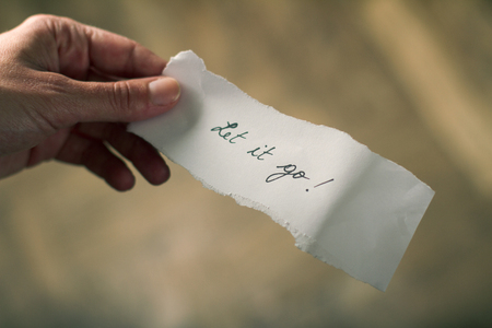 let: Hand holding a note of paper with the message let it go written on it Stock Photo
